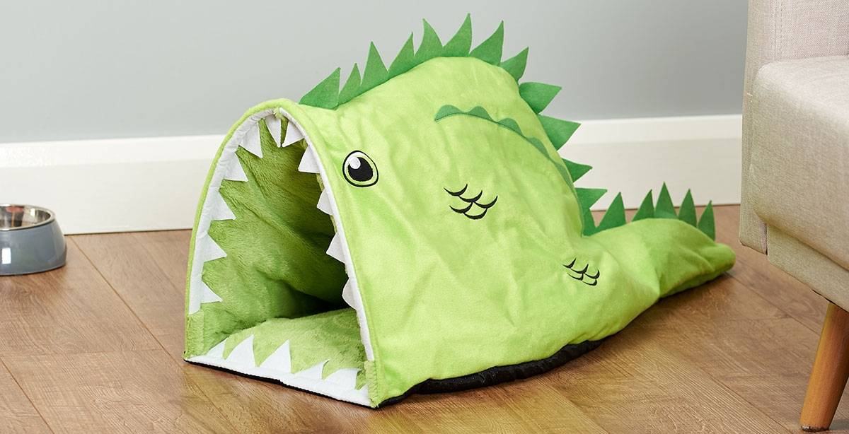 crocodile shaped pet bed in a living room with wooden flooring